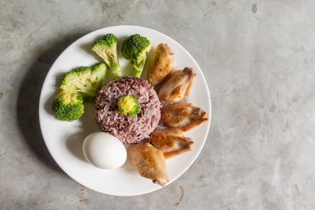 Saubere nahrung, gebratenes huhn, brokkoligemüse, ei und reis