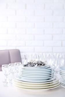 Saubere teller, gläser und besteck auf weißem tisch