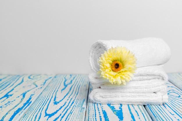 Saubere weiche handtücher mit blume auf holztisch
