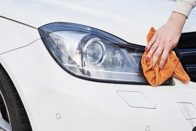 Sauberer autoscheinwerfer der frau mit mikrofasertuch