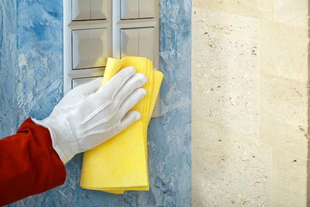 Sauberer lichtschalter der frau mit tuch auf grauer betonwand hand in handschuhdesinfektionsflächen mit gelbem lappen. das neue normale covid-coronavirus in der reinigung.