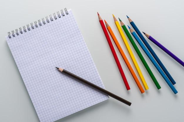 Sauberer notizblock in einem käfig mit einem darauf liegenden bleistift und regenbogenfarbstiften auf weißem hintergrund