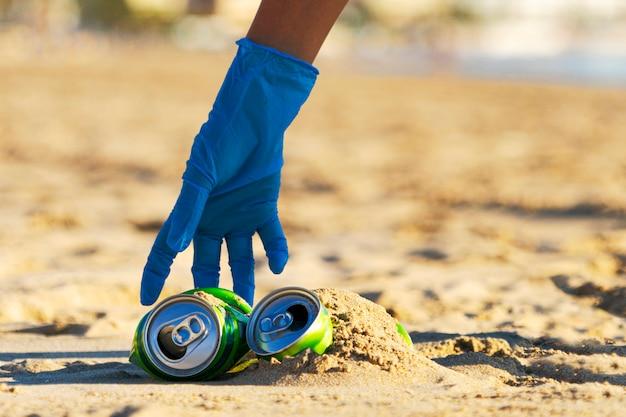 Sauberer strand vom müll. frau hand, die leere alkoholfreie getränkedosen müll vom strand aufnimmt