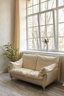 Sauberes familienzimmer mit weißer ledercouch und großem fenster