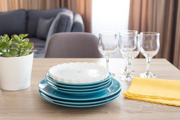 Sauberes geschirr auf dem tisch. gestapelte saubere blaue und weiße teller, gläser und gelbe servietten auf holztisch in der küche.