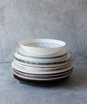 Sauberes geschirr auf dem tisch in einem stapel auf einem grauen hintergrund