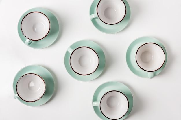 Sauberes geschirr, kaffee- oder teeservice. viele elegante hellblaue tassen und untertassen aus porzellan, high key, draufsicht und flache lage.