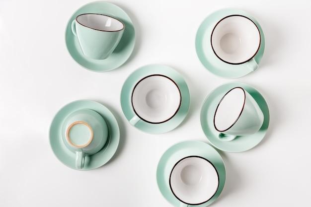 Sauberes geschirr, kaffee- oder teeservice. viele elegante hellblaue tassen und untertassen aus porzellan, high key, draufsicht und flache lage. Premium Fotos