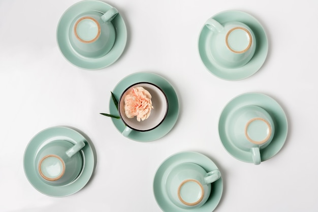 Sauberes geschirr, kaffee- oder teeservice. viele elegante porzellantassen und untertassen mit blumen im inneren, high key, draufsicht und flacher lage.