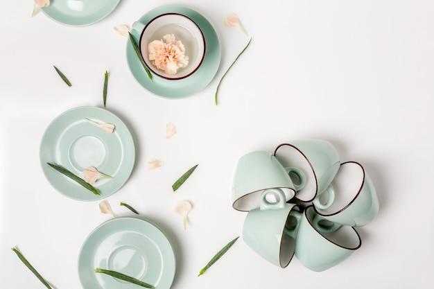 Sauberes geschirr, kaffee- oder teeservice. zusammensetzung aus eleganten porzellantassen und untertassen mit blütenblättern, high key, draufsicht und flachlage.