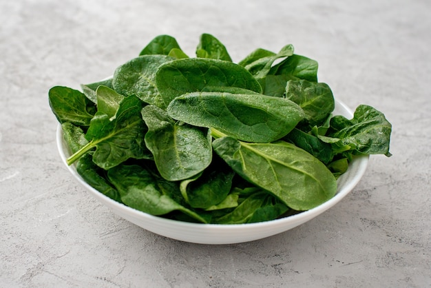 Sauberes lebensmittelkonzept. blätter des frischen organischen spinatgrüns in einem teller auf hellem hintergrund. gesunde entgiftungs-frühling-sommer-diät. veganes rohkost.