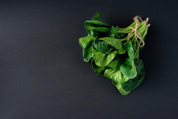 Sauberes lebensmittelkonzept. bündel blätter des frischen organischen spinatgrüns auf einem schwarzen hintergrund. gesunde entgiftungs-frühling-sommer-diät. veganes rohkost. speicherplatz kopieren.