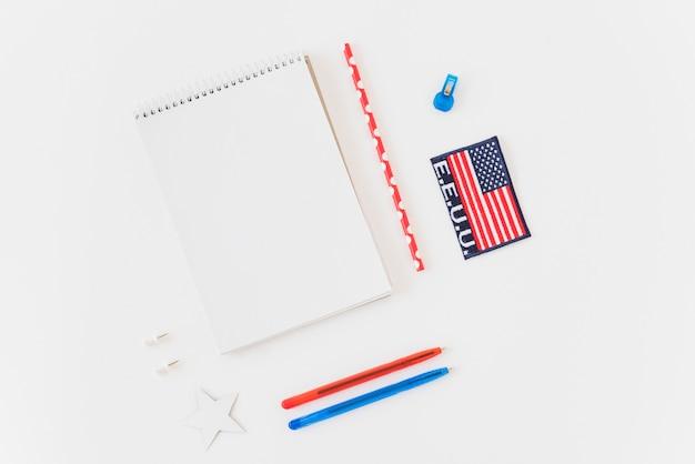 Sauberes notizbuch mit stiften und amerikanischer flagge