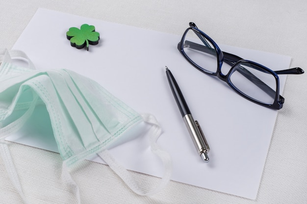 Sauberes papier, ein grünes kleeblatt und eine schutzmaske