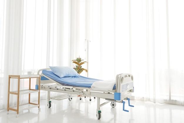 Sauberes und klares leeres krankenhaus nahe sonnigem fenster, blaue bettwäsche mit weißem vorhang im stationsraum für hintergrund