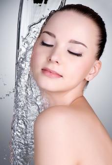 Sauberes wasser auf schönen weiblichen gesicht und körper