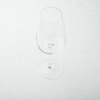 Sauberes weinglas-set im quadratischen format auf weißem steintisch