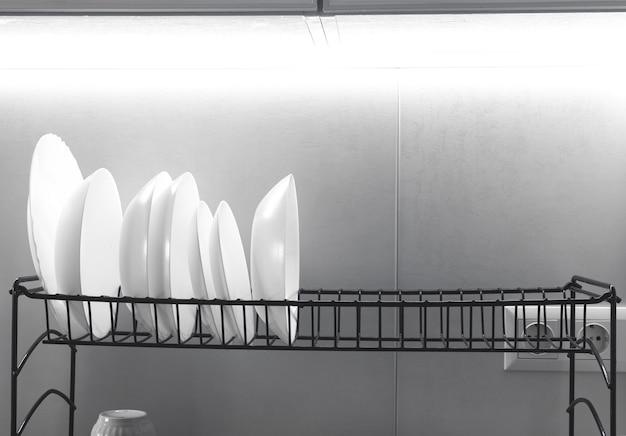 Sauberes weißes geschirr, das auf einem metallgeschirrständer auf einem hellen küchenhintergrundfoto trocknet