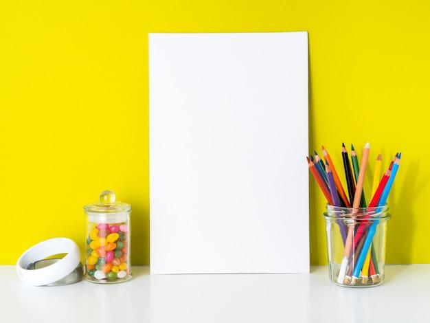 Sauberes weißes segeltuch des modells, farbige bleistifte auf hellem gelbem hintergrund. für kreativität, zeichnen.