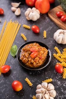 Sauce zum braten von spaghetti oder zum braten von makkaroni auf einem schwarzen teller.