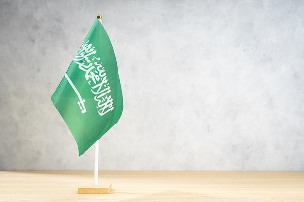 Saudi-arabien-tischflagge auf weißer strukturierter wand. kopieren sie platz für text, designs oder zeichnungen
