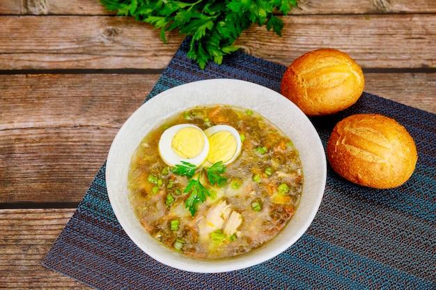 Sauerampfer-suppe mit ei und knusprigen brötchen