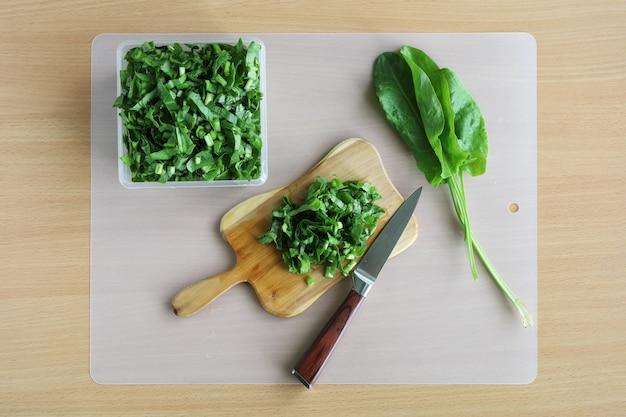 Sauerampfersalat auf schneidebrett und messer auf tisch geschnitten, vitamine für vegetarier