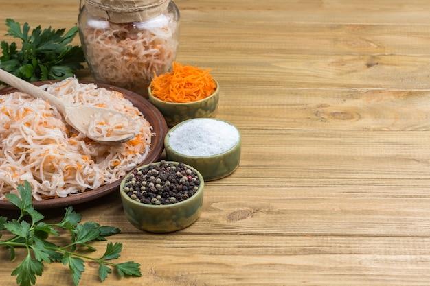 Sauerkraut auf teller, geriebene rohe karotten, petersilie, salz und gewürze. hausgemachte fermentationsprodukte. gesunde winterernährung. helle holzoberfläche. speicherplatz kopieren