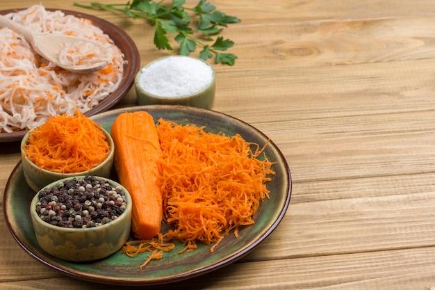 Sauerkraut auf teller, geriebene rohe karotten, petersilie und salz. hausgemachte fermentationsprodukte. gesunde winterernährung. helle holzoberfläche. speicherplatz kopieren