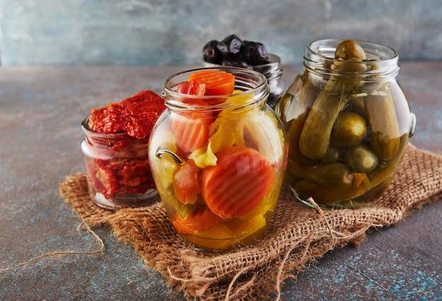 Sauerkraut, eingelegte karotten, eingelegte gurken, eingelegte oliven und oliven, getrocknete tomaten in gläsern