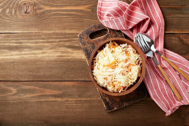 Sauerkraut, fermentierter kohl mit karotten in der schüssel auf hölzernem hintergrund mit kopienraum. superfoods zur unterstützung des immunsystems. draufsicht, flach liegen