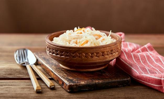 Sauerkraut, fermentierter kohl mit karotten in der schüssel auf hölzernem hintergrund. superfoods zur unterstützung des immunsystems.