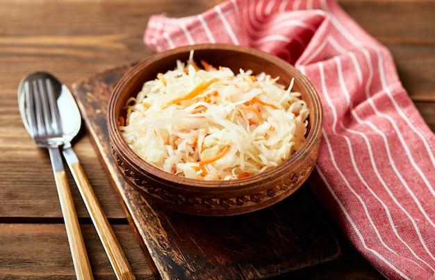 Sauerkraut fermentierter kohl mit karotten in schüssel auf holzhintergrund mit kopierraum