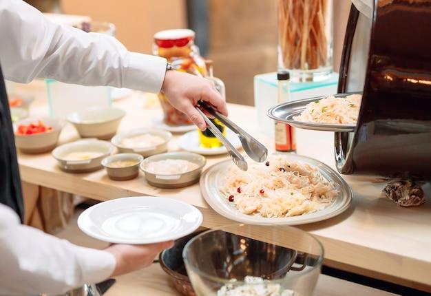 Sauerkraut. frühstück im hotel oder restaurant. der kellner legt das sauerkraut in die schüssel.