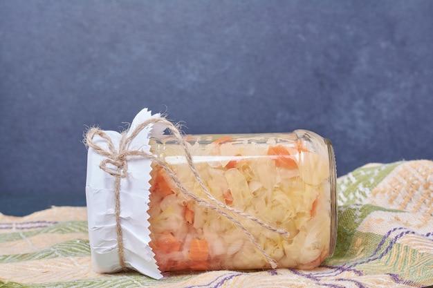 Sauerkraut im glas auf blau mit tischdecke.