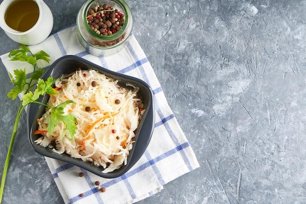Sauerkraut mit gewürzen in der grauen schüssel. natürliche probiotika, gesunde ernährung