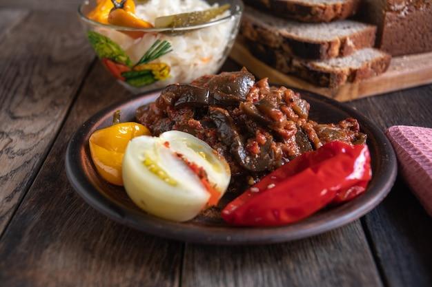 Sauerkraut-tomaten-gurke und paprika in einer glasschüssel auf einem holztisch hausgemachte gurken