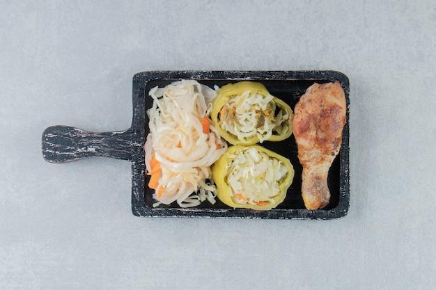 Sauerkraut und gebratenes hühnerbein auf schwarzem brett.