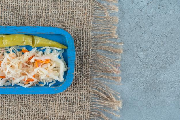 Sauerkraut und paprika in dosen auf einer holzplatte auf textur, auf dem marmortisch.