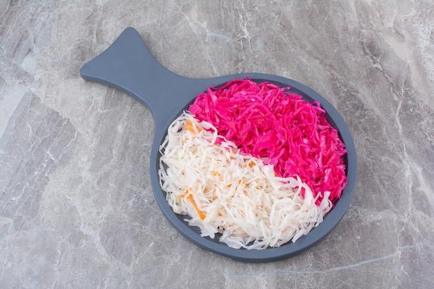 Sauerkraut und rotkohl auf schwarzem holzbrett.