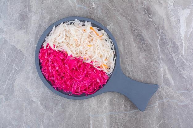 Sauerkraut und rotkohl auf schwarzem holzbrett