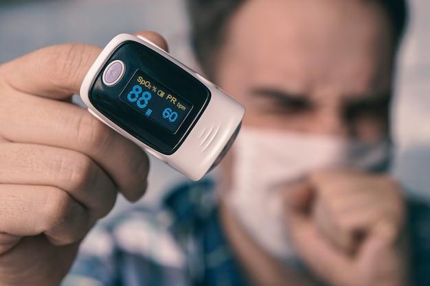 Sauerstoffsättigung des blutes. pulsoximeter am finger eines mannes. ein patient in einer medizinischen maske misst die blutsättigung mit einem elektronischen pulsoximeter an seinem finger. geringe sättigung des blutes.
