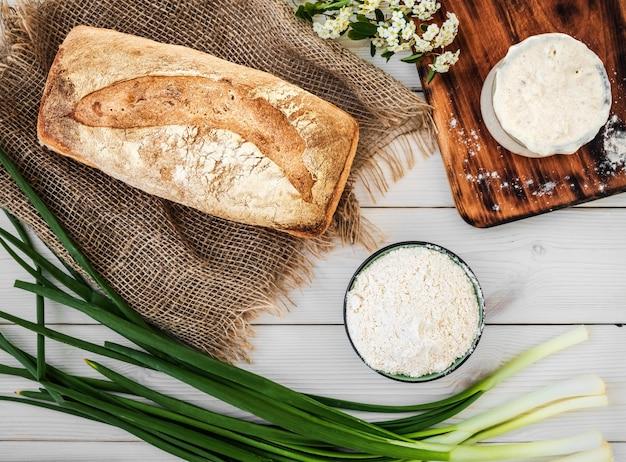 Sauerteig für die zubereitung von brot, mehl und frisch gebackenem brot auf einem weißen holztisch