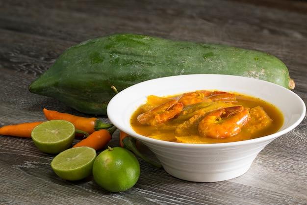 Saure currygarnele und grüne papaya auf holz.