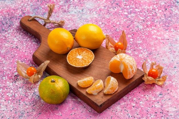 Saure frische mandarinen der vorderansicht mit zitronen auf rosa hintergrund.