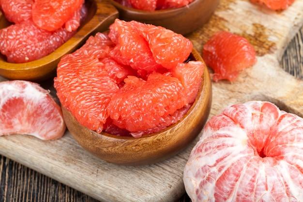 Saure reife grapefruit geschält und in scheiben geteilt, rosa grapefruit essfertig, nahaufnahme Premium Fotos