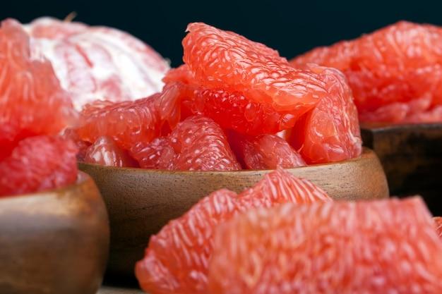 Saure reife grapefruit geschält und in scheiben geteilt, rosa grapefruit essfertig, nahaufnahme