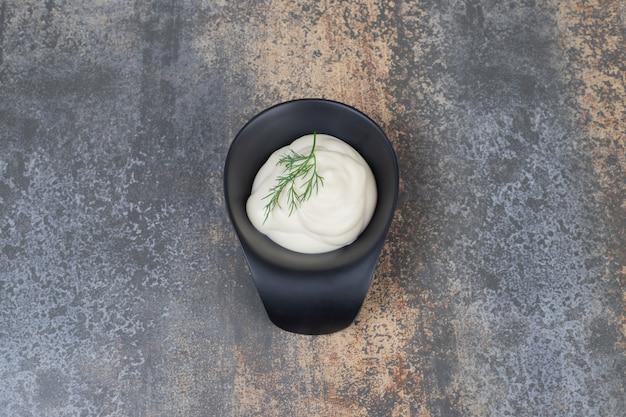 Saure sahne mit gemüse auf teller auf marmoroberfläche.