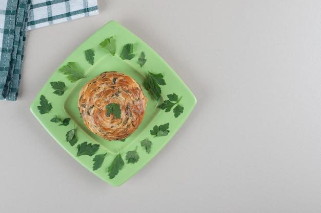 Saure süßigkeiten auf einer platte mit petersilienblättern auf marmorhintergrund verziert.