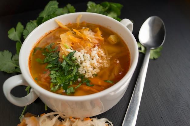 Saure suppe mit cilantro auf einem schwarzen hintergrund